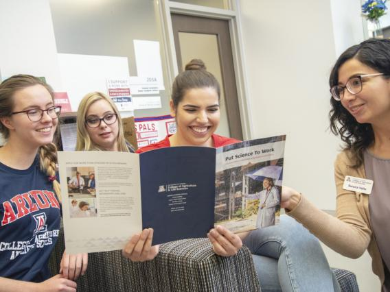 College advisor shares brochure with three students.