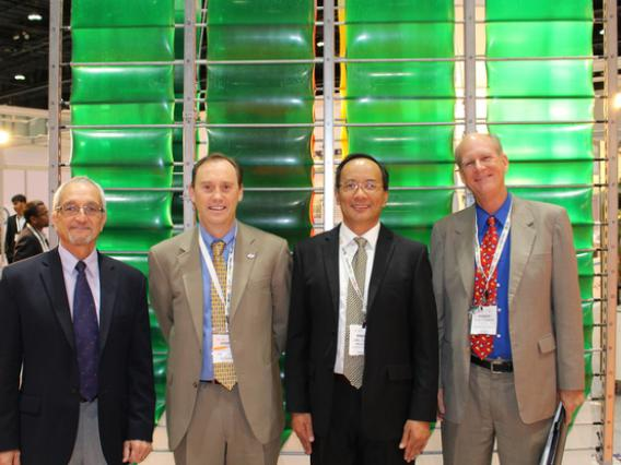 Four men in suits standing in front of Accordion photobioreactor