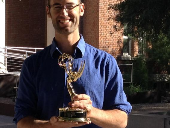 Man holding Emmy Award in front of brick university building