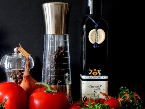 Pepper grinders and a bottle of olive oil with tomatoes in the foreground