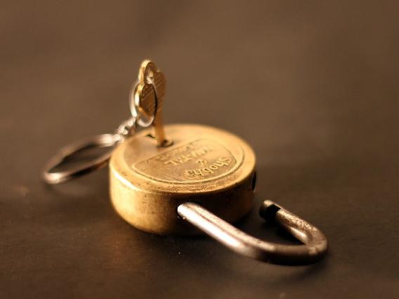 Gold-tone padlock with key inserted