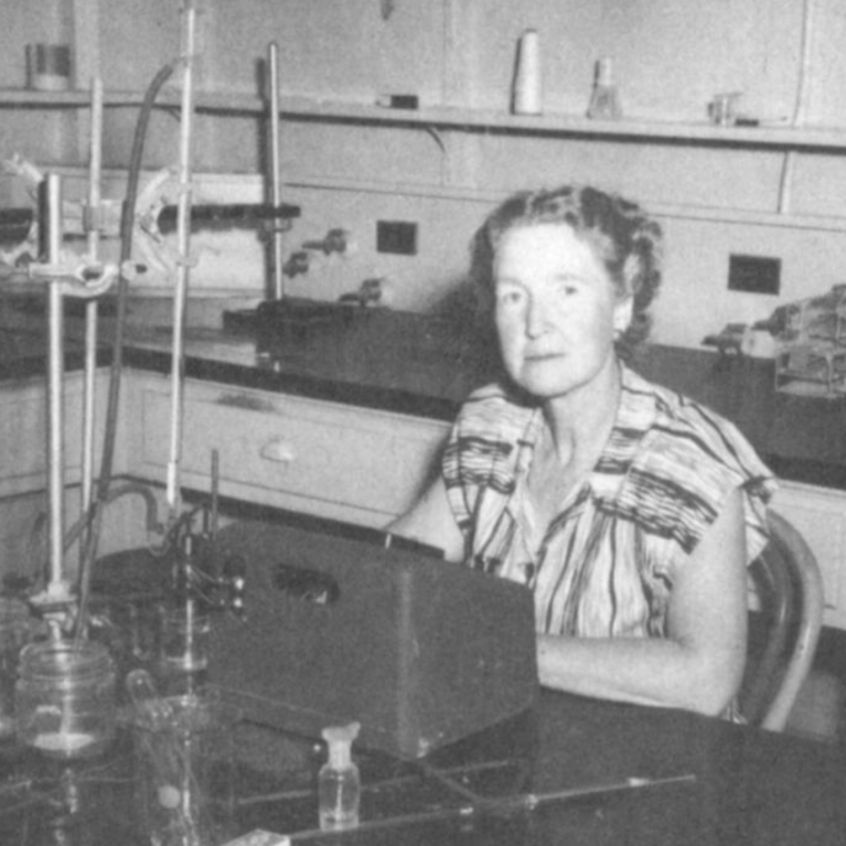 Black and white photo of scientist seated in lab.